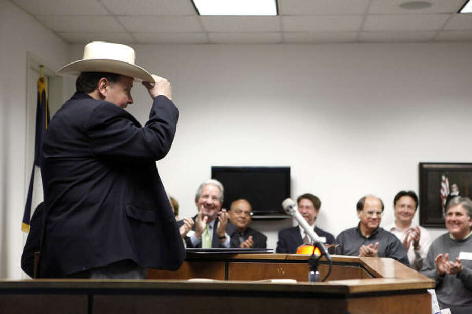Former Harris County Attorney Mike Driscoll, left, tries on a hat presented to him Friday during the dedication of the Mike Driscoll Courtroom downtown, Photo: Todd Spoth, Chronicle