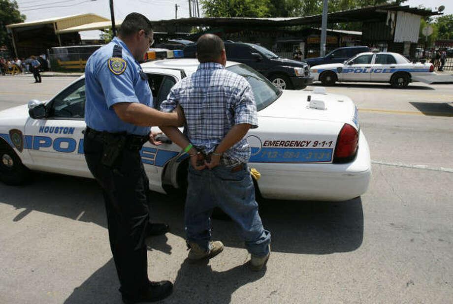 Un hombre es introducido a una patrulla del Departamento Policial de Houston tras ser arrestado por presunto fraude de documentos en el mercado de pulgas Sunny Flea de la zona de Airline, en Houston. Photo: Julio Cortez, Houston Chronicle