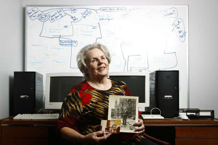 Margie Seaman, president of Citation Solutions, a Web design firm, holds a photo of a brother and his 1970s computer. Seaman has immersed herself in today's technology. Photo: Michael Paulsen :, Chronicle