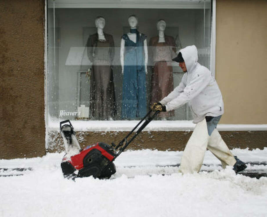 Toby Sumner, of Ritzman Lawn Service, clears snow in front of a Weaver's Department Store window in Lawrence, Kan., on Saturday. Photo: Orlin Wagner, Associated Press