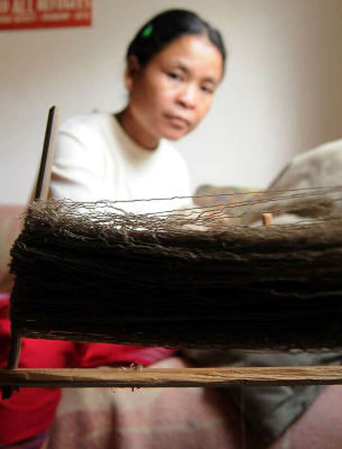 Beh Meh unravels a spool of weaving thread during a Community Cloth open house. Community Cloth is an initiative encouraging refugee women in Houston to use their skills to help support their families. Photo: DAVE ROSSMAN