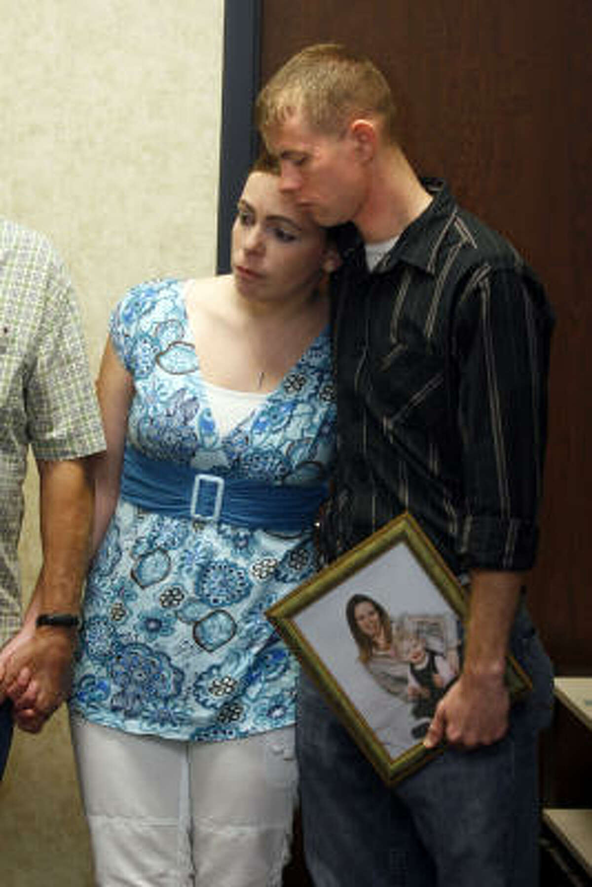 Jimmy Goodson, holding a picture of his sister Bridgette Gearen, is joined by his wife, Amanda, during a July 2007 Galveston news conference. Gearen, of Orange, was raped, beaten and strangled near her Bolivar Peninsula vacation beach house. No arrests have been made.