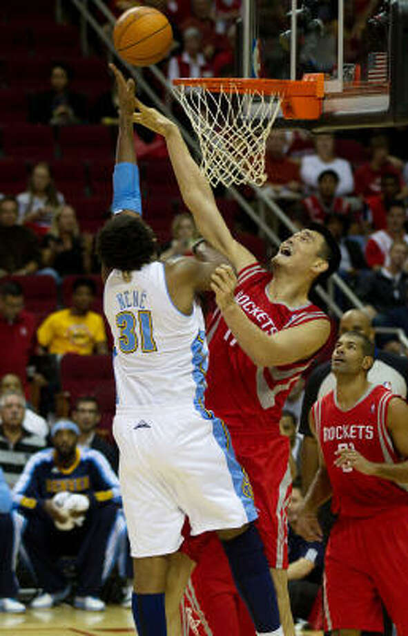 Rockets center Yao Ming blocks a shot by Nuggets center Nene during the first half on Saturday. Photo: Smiley N. Pool, Chronicle