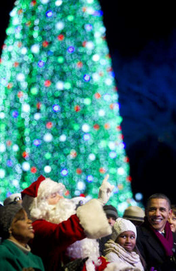 "President Barack Obama, joined by mother-in-law Marian Robinson, from left, ""Santa Claus"" and Obama's daughter Sasha, enjoys the National Christmas Tree lighting ceremony Dec. 9 in Washington, D.C. Photo: Andrew Harrer, Bloomberg"