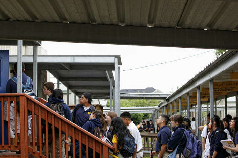 Students wait in line to enter their speech classroom in between rows of temporary buildings, at the Southeast campus of the YES prep school in south Houston. Photo: Todd Spoth, Chronicle