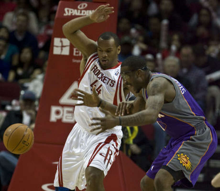 Rockets center Chuck Hayes and Suns center Amar'e Stoudemire chase a loose ball in front of the basket. Photo: James Nielsen, Chronicle