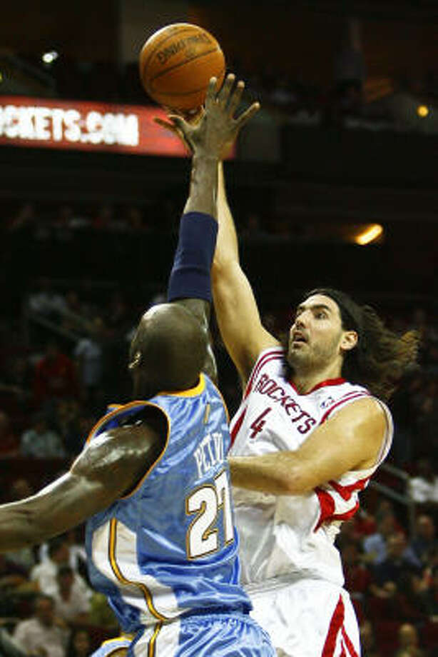 Rockets forward Luis Scola puts up a shot over Nuggets center Johan Petro. Photo: Michael Paulsen, Chronicle