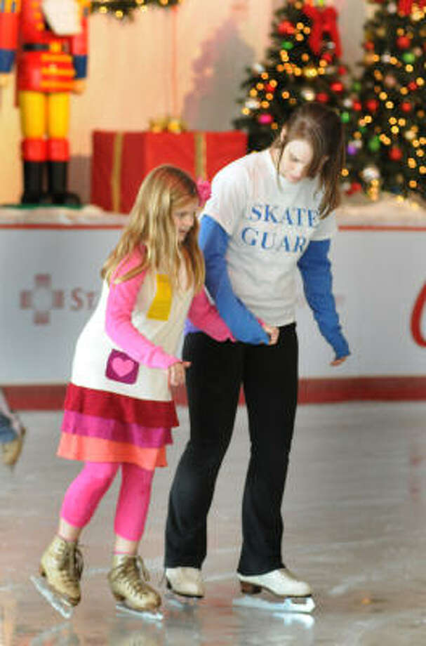 DAVID HOPPER: FOR THE CHRONICLE ON THE ICE: Avery Grace Garnett, of The Woodlands, skates with Ice Rink skating guard Julia Dupree, of Tomball, during the preview weekend opening at the Ice Rink at The Woodlands Town Center. Photo: David Hopper, For The Chronicle
