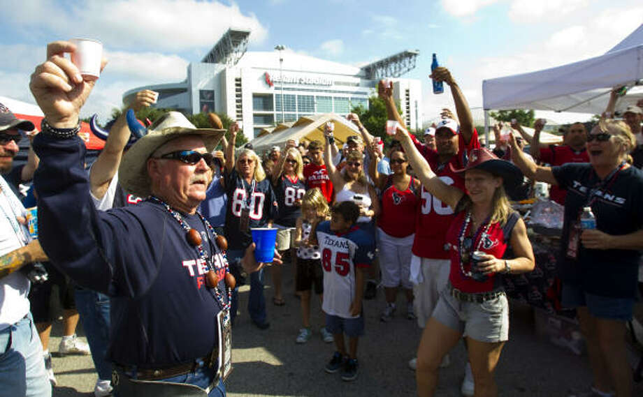 A group of Texans fans raise a glass as they tailgate in the parking lot outside Reliant Stadium. Photo: Brett Coomer, Chronicle