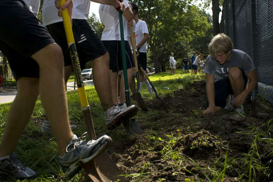 Jack Kempner,16, a junior at St. John's School, works on one of his final Boy Scout service projects with a group of volunteers he organized. The project, landscaping and cleaning up the tennis courts at Pumpkin Park, will  help him earn the ranking of Eagle Scout. Photo: Johnny Hanson, Chronicle