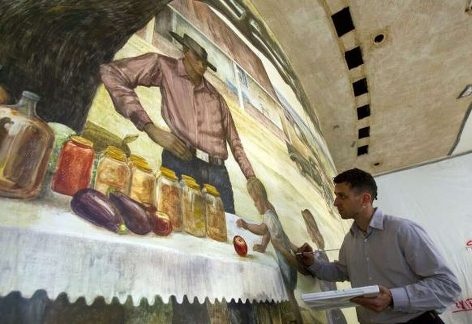 Kuvalesaya Zakheim works on restoring the fresco — painted in 1952 by Peter Hurd — in the foyer of the M.D. Anderson Cancer Center administration building. Photo: Johnny Hanson, Houston Chronicle