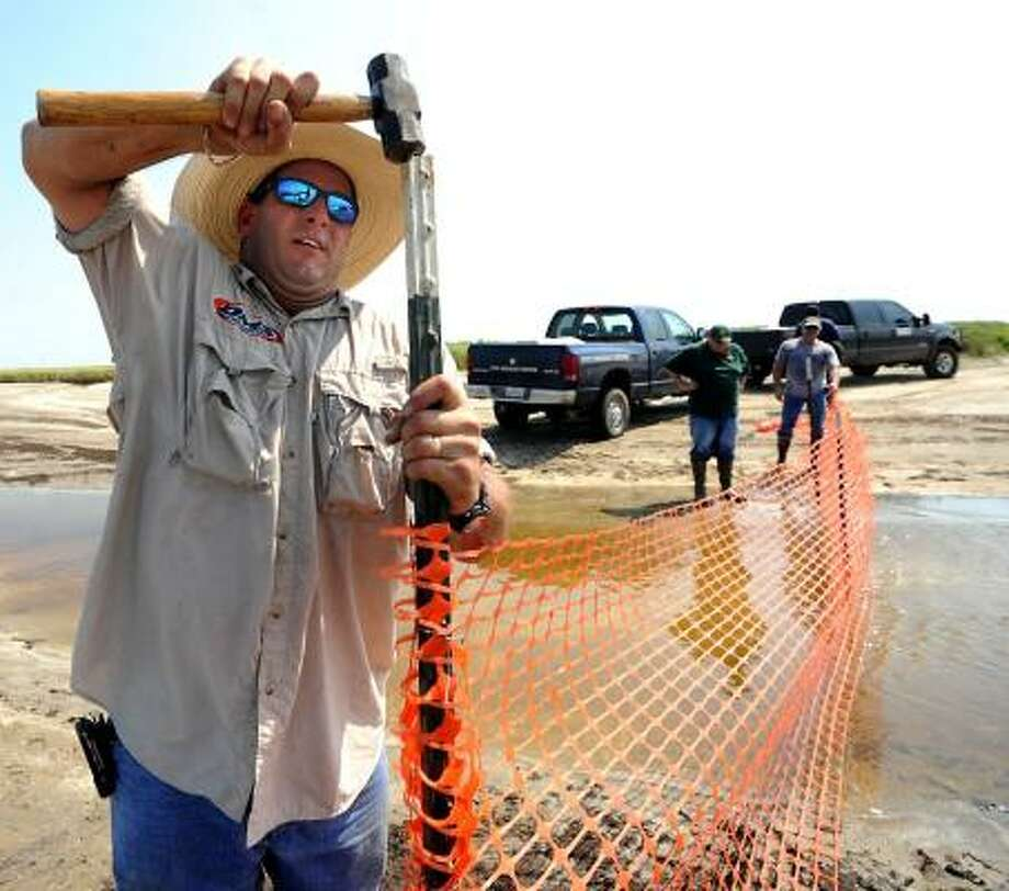 Duke Daigle, of Miller Environmental, secures barricade fencing on Saturday to prevent oil from getting into one of the tidal inlets that lead into the wetlands at Sea Rim State Park. Photo: Tammy McKinley, Beaumont Enterprise
