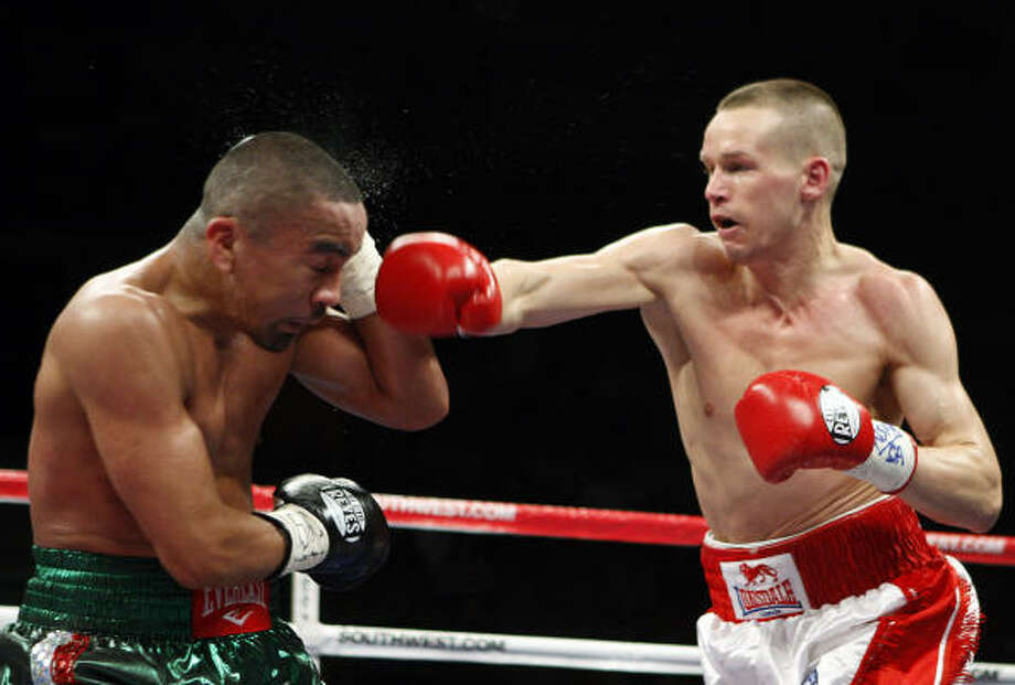 Houston's Rocky Juarez takes a punch from Jason Litzau during their super featherweight bout. Photo: Isaac Brekken, AP