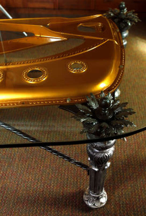 Weber designed the legs from a salvaged iron fence and added metal blooms. The piano's cast-iron plate, called a harp, was painted to match the original gold color. Photo: Melissa Phillip, Chronicle