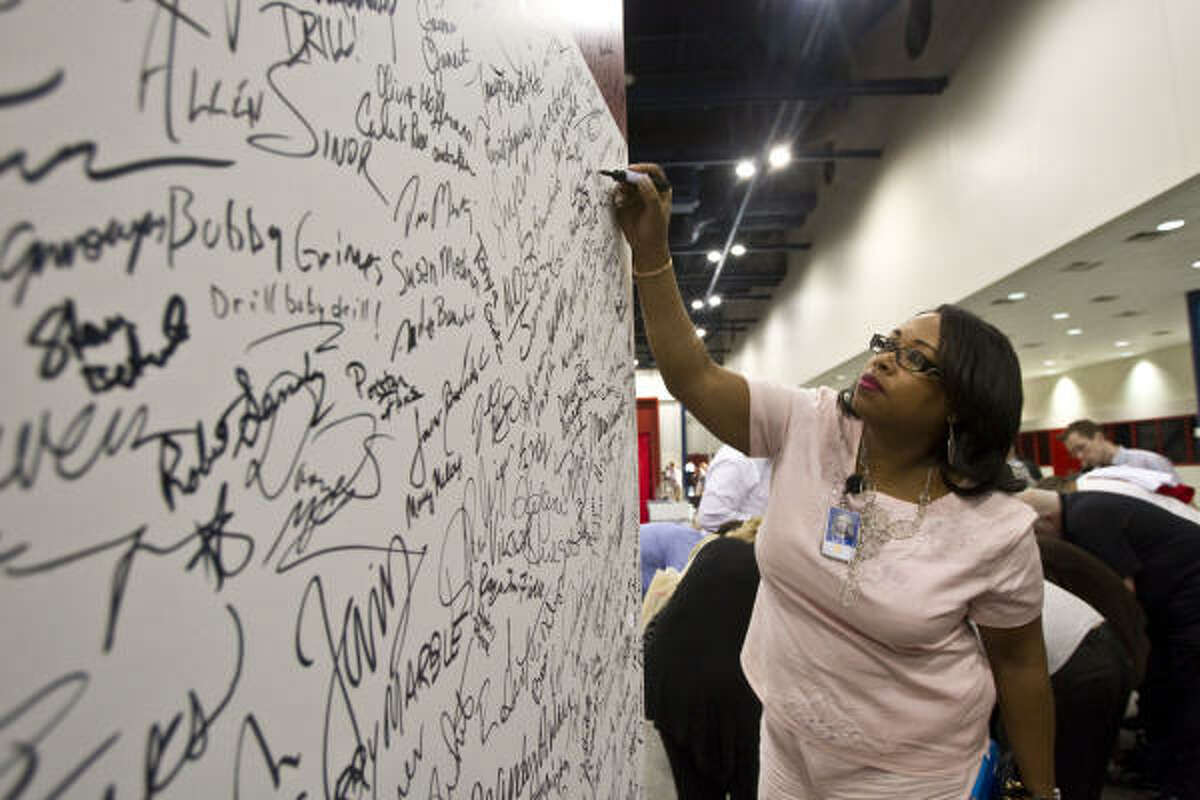 Tujuana Taplin signs a large board addressed to Texas members of Congress on Wednesday during an energy rally at the George R. Brown Convention Center. The event drew employees from large and small energy companies.