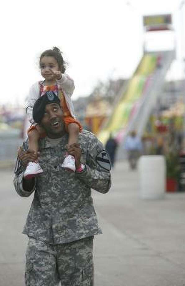 Joshua Union, 24, carries his 2-year-old, Gabriella, around the midway Wednesday during the Houston Livestock Show and Rodeo's third annual Support the Troops Day. Photo: Mayra Beltran, Chronicle