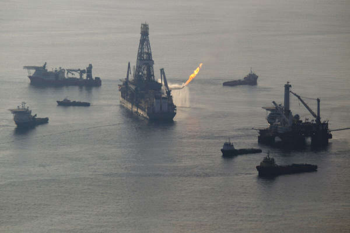 The Discoverer Enterprise, encircled by support vessels, continues to ride at anchor over the site of the Deepwater Horizon accident. This photo, from on board a government P-3 aircraft, shows natural gas being burned off during recovery. Early Wednesday, lightning caused a small fire on the derrick and shut down the operation for a while. No one was hurt.
