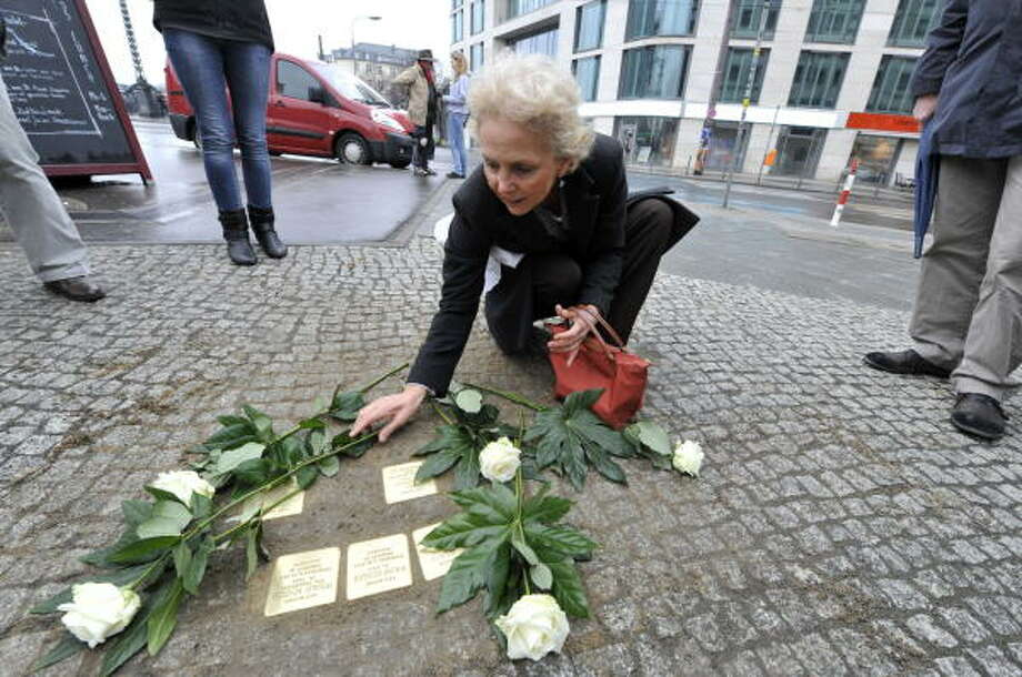 Dagmar Gropper lays flowers on 'stolpersteine,' or stumbling stones, in Berlin's Friedrichstrasse in March. The stones, topped with small brass plaques, are installed in front of houses where Jews who were deported to death camps during Germany's Nazi regime lived. Photo: JOHN MACDOUGALL, AFP | Getty Images