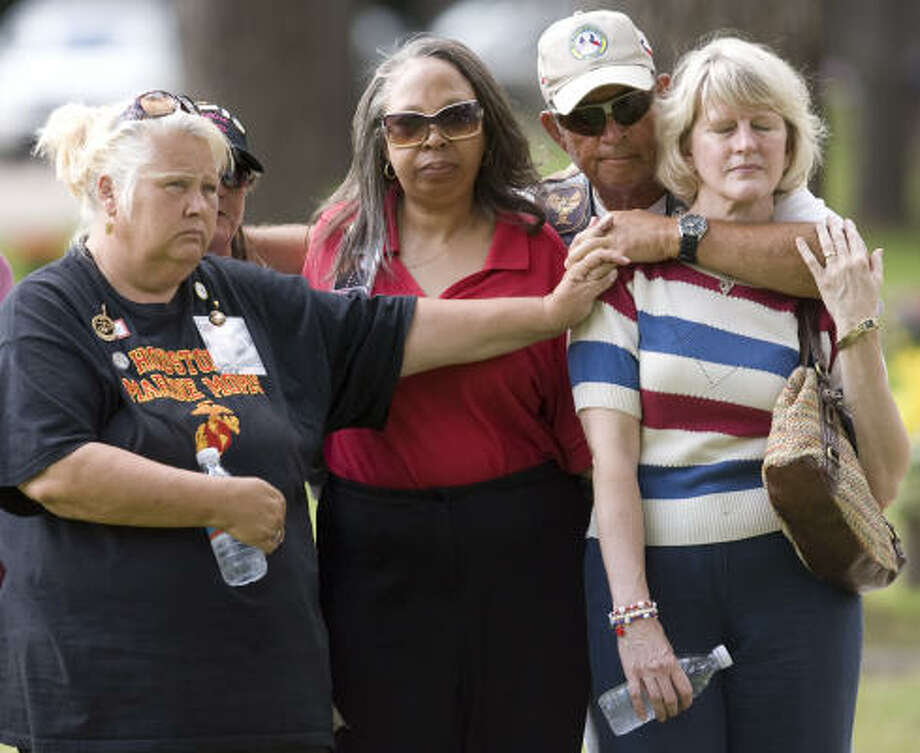 Sharon Ferguson, left, Robin Graham, (partially hidden), Karan McKoy and Becky Sutjak mourn with Patriot Rider Jerry Sorsdal during services for Marine Cpl. Jeffrey Johnson. Photo: Billy Smith II, Chronicle