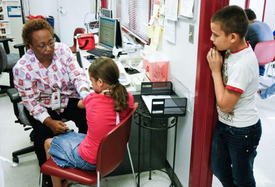 Javier Carcamo waits as Rosalind Bowie gives his sister, Amanda, a shot Wednesday at the La Nueva Casa de Amigos Health Center. Photo: Nick De La Torre, Chronicle