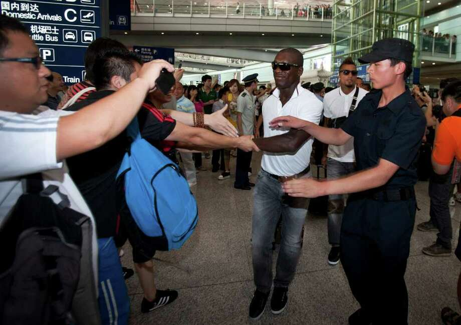 A security guard tries to stop Chinese fans from shaking hand with AC Milan soccer player Clarence Seedorf as he and his team arrive at the Beijing Capital International Airport in Beijing, China, Tuesday, Aug. 2, 2011.  AC Milan will play with Inter Milan at the Italian Super cup soccer match in Beijing Saturday. (AP Photo/Andy Wong) Photo: Andy Wong, STF / AP