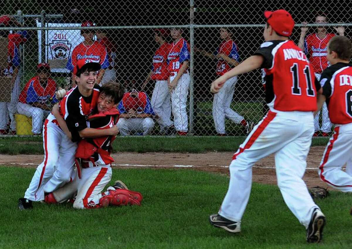 Fairfield American's pitcher Jack Oricoli, left, and catcher Aidan Kudzy embrace as the rest of the team rush onto the field after beating Glastonbury in the state little league baseball championship in Prospect, Conn. on Tuesday August 2, 2011.