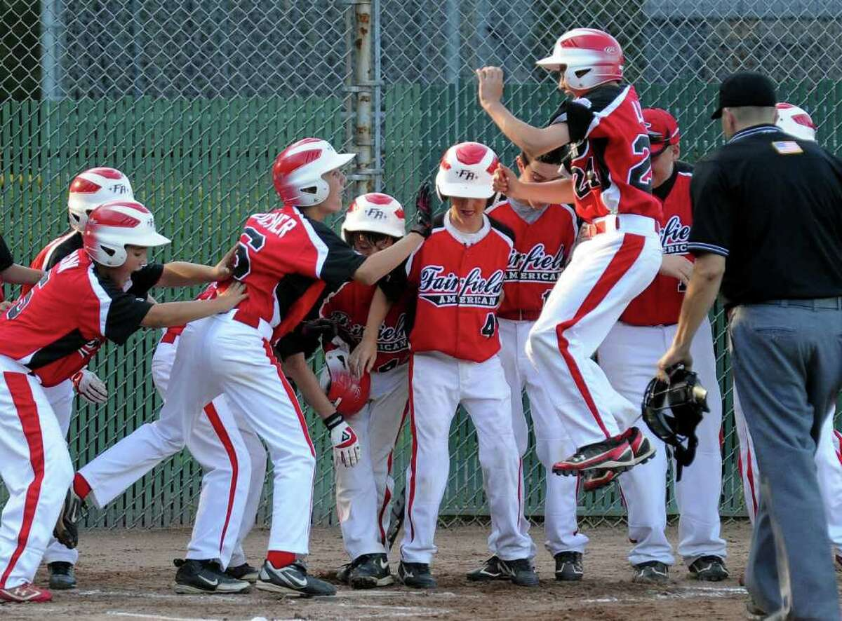 Fairfield American teammates wait to greet Brendan Layne as he leaps into the air to land on home plate after hitting and home during the state little league baseball championship against Glastonbury in Prospect, Conn. on Tuesday August 2, 2011.