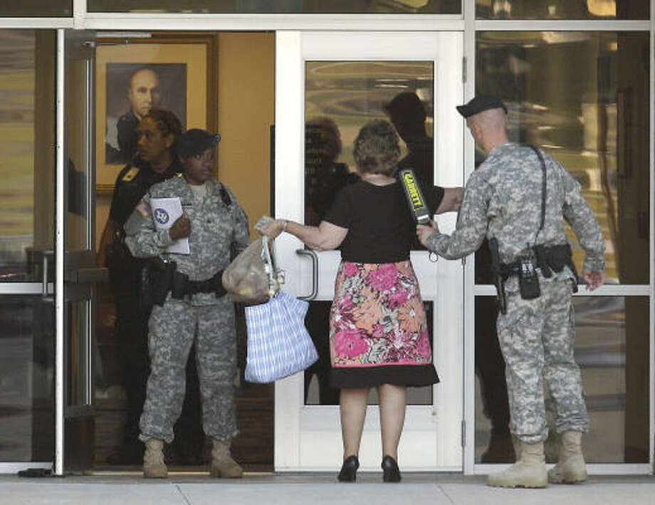 A woman goes through security as she arrives at the courtroom on Fort Hood, where a hearing for Maj. Nidal Malik Hasan was held Tuesday. Photo: Eric Gay, AP