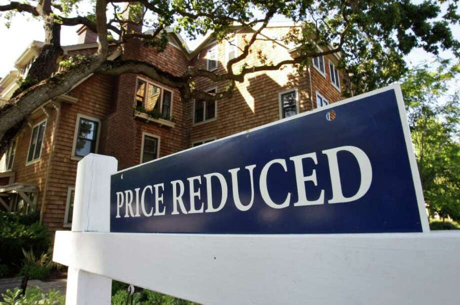 """In this photo taken July 7, 2011, a """"Price Reduced"""" sign is displayed on a house in Palo Alto, Calif. Americans cut their spending in June for the first time in nearly two years.  (AP Photo/Paul Sakuma) Photo: Paul Sakuma, AP / AP"""