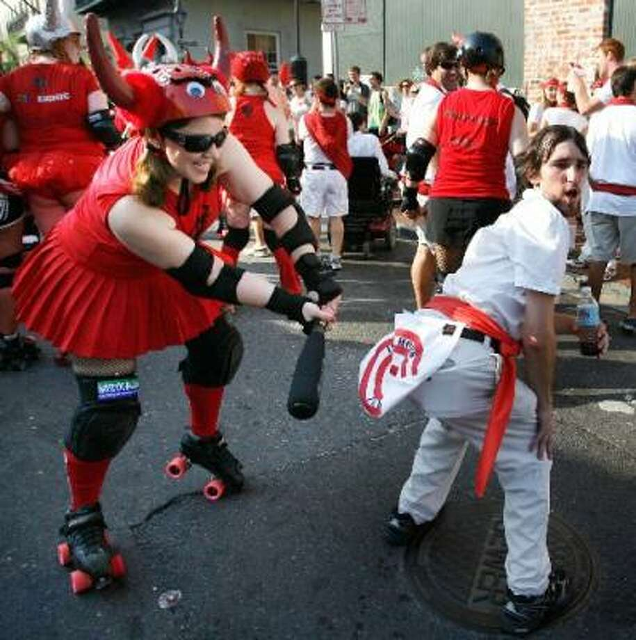"Heather Link takes aim on the hindquarters of Adam Verrett during a tongue-in-cheek version of the running of the bulls in New Orleans on Saturday. ""San Fermin in Nueva Orleans"" kicked off Saturday in the French Quarter. Photo: John McCusker, The Times-Picayune"