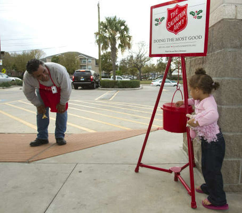 "Earnest ""Chico"" Duran thanks Laila Colello, 2, for her contribution Friday at the Walgreen's on Washington at Studemont. The Salvation Army says hard times increase donations. Photo: Brett Coomer, Chronicle"