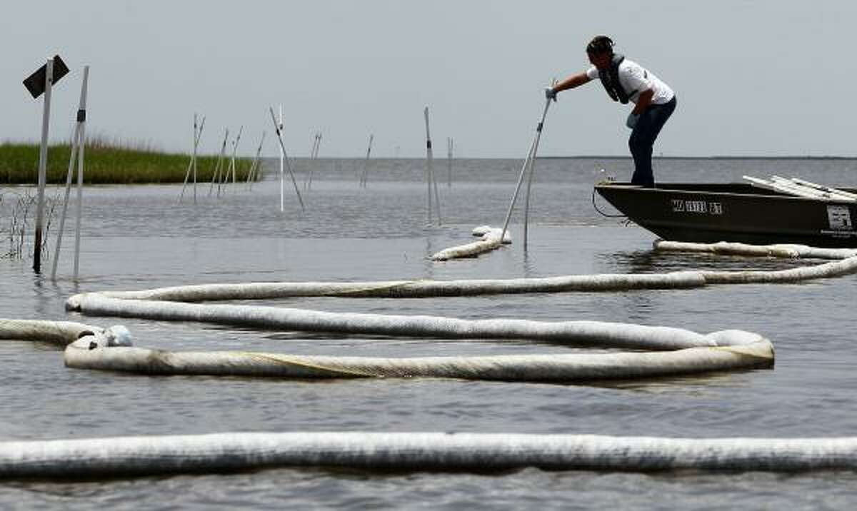 A worker adjusts an oil boom in Louisiana in the area where the Pointe Aux Chenes tribe lives. The tribe is concerned about leakage spotted near BP's newly installed oil well cap.