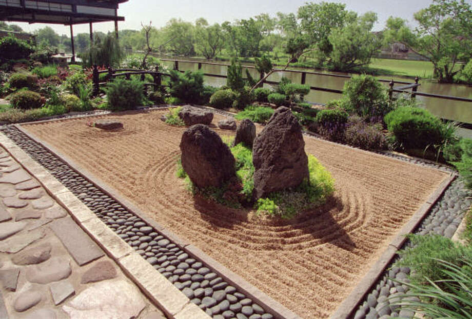 "In this Terry Vekris-designed Zen garden, a rectangular bed of raked gravel is edged in polished limestone and blue-black moonrock. The gravel, representative of a body of water, is raked into calming straight lines and in concentric circles, representing rippling movement around an ""island"" of low-growing juniper and three boulders. Photo: JOHN EVERETT"