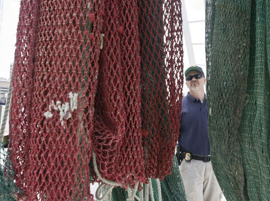 NOAA Special Agent Charles Tyer inspects a shrimp net in Galveston as he explains the operation of a turtle excluder device, which is supposed to protect sea turtles. Photo: James Nielsen, Chronicle