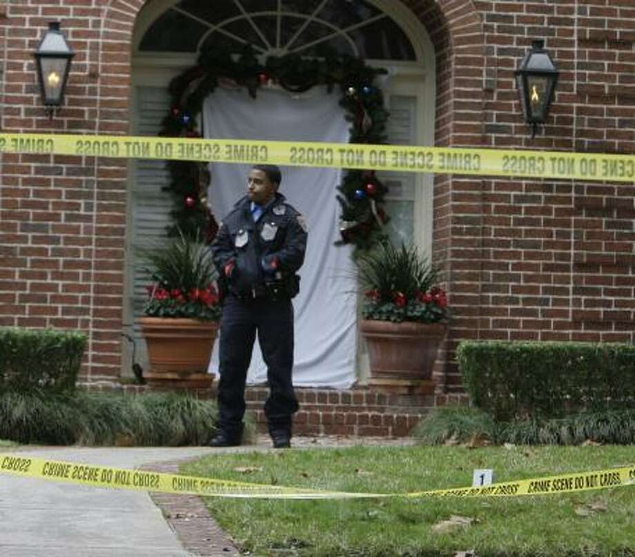 A Houston Police officer stands guard Wednesday at the crime scene in the Royden Oaks subdivision. Photo: James Nielsen, Chronicle