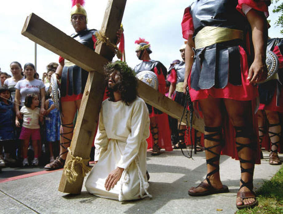 Juan Carlos Montoya, playing Jesus, falls to his knees as he carries a wooden cross during a play in Spanish depicting the Stations of the Cross on Good Friday in 2003. Photo: Joshua Trujillo, Chronicle File