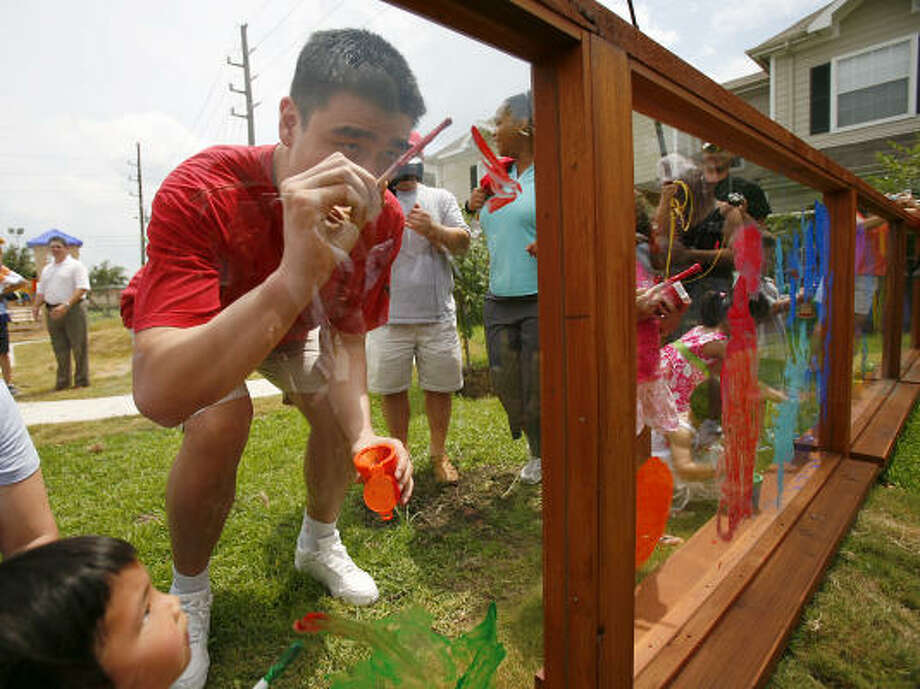 Rockets center Yao Ming helps children decorate on Saturday during the unveiling of a nature-based playground at the Chinese Community Center. Photo: Nick De La Torre, Chronicle
