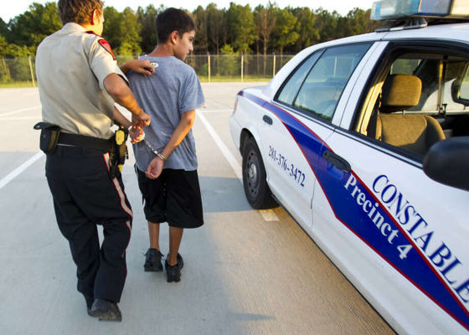 Erik Fuente, 13,  a member of the Law Enforcement Explorers Post 901 in Spring, is handcuffed by Walter Gabriel, 15, with Post 26, during a traffic-stop scenario. Photo: Karen Warren, Chronicle