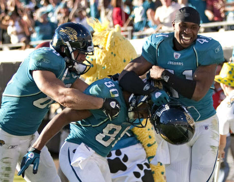 Jaguars tight end Zach Miller, left, wide receiver Mike Thomas (80), and cornerback Tyron Brackenridge celebrate Thomas's 50-yard touchdown reception on the final play Sunday. Photo: Brett Coomer, Chronicle