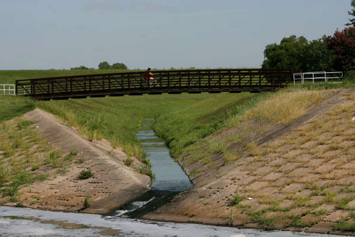 A biker hits the bridge at the edge of George Bush Park and Terry Hershey Park's hike-and-bike trail Friday. Green space could be a more familiar sight if two Houston business groups get their way.