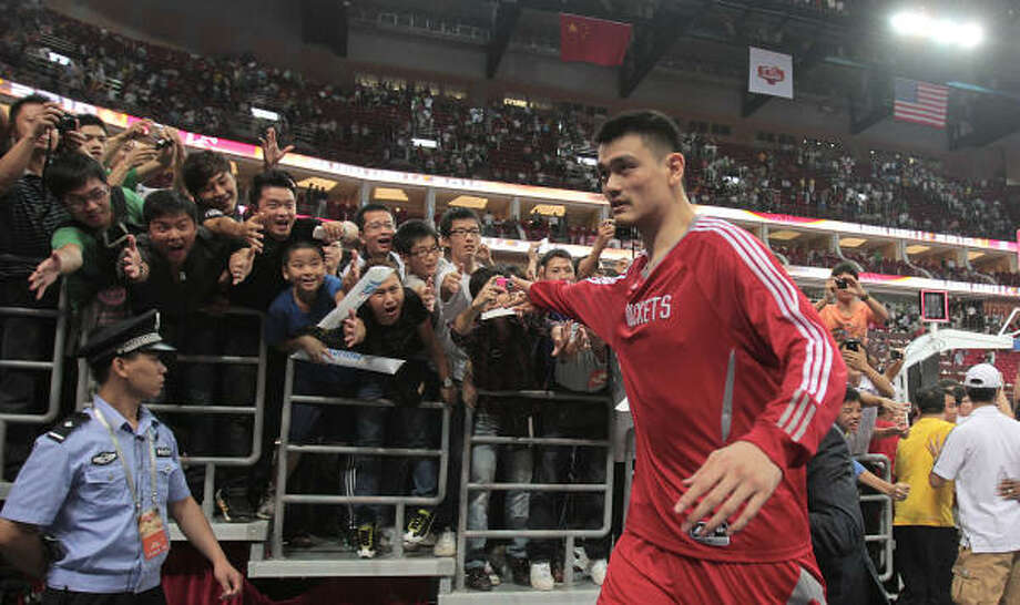 Center Yao Ming, who was born in Shanghai, says goodbye to his fans after the Rockets defeated the Nets 95-85 in Saturday's preseason game at the Guangzhou International Sports Arena. Yao's popularity is unparalleled in his homeland. Photo: Billy Smith II, Chronicle