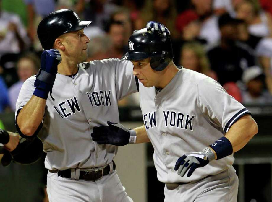 New York Yankees' Derek Jeter, left, congratulates Mark Teixeira after they both scored on Teixeira's two-run home run against the Chicago White Sox during the third inning of a baseball game Tuesday, Aug. 2, 2011, in Chicago. (AP Photo/John Smierciak) Photo: John Smierciak
