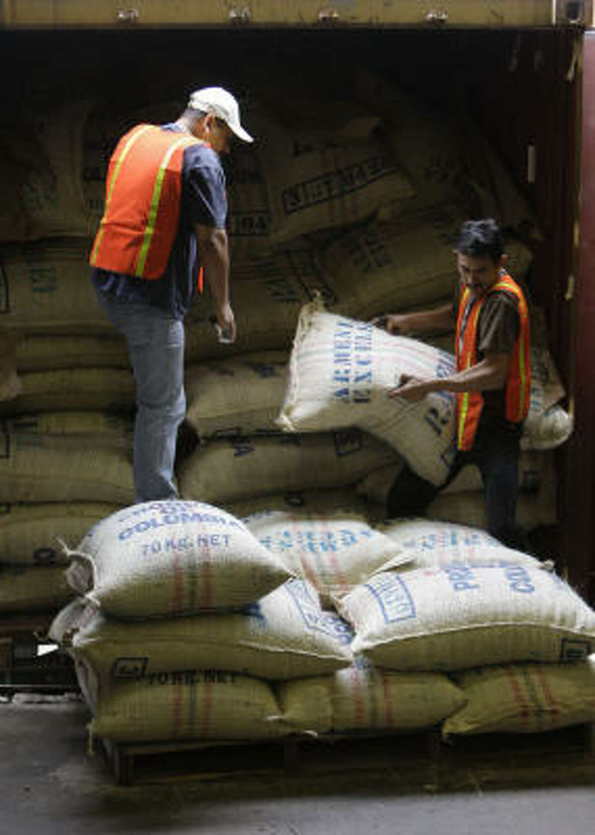 Arturo Reyes, left, and Roberto Hernandez unload Colombian coffee bags from a trailer at Gulf Winds International. An inventory tax exemption has helped the coffee trade grow in Houston.