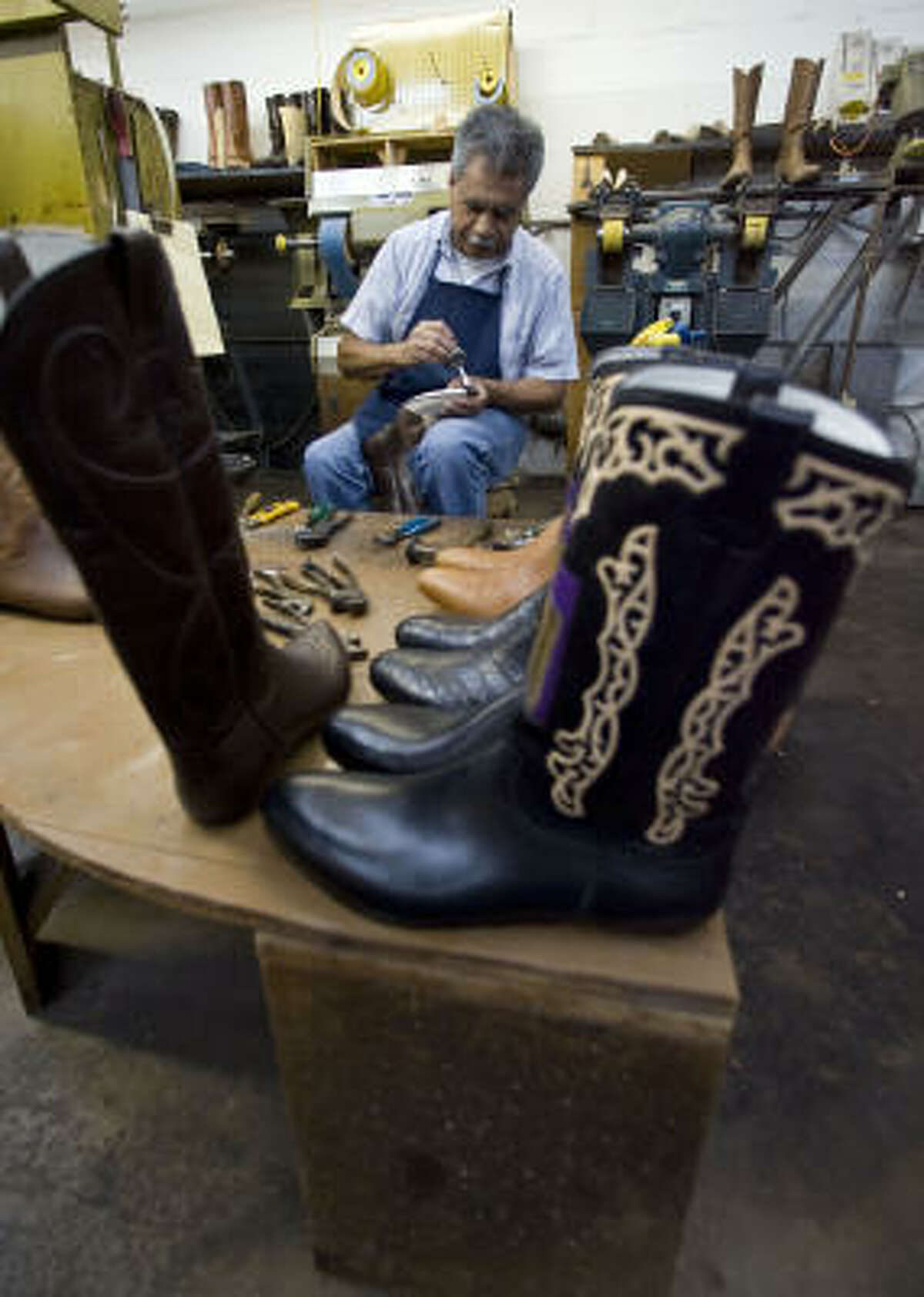 Jorge Amaro works on a pair of boots at the Wheeler Boot Co. T.J. Farnsworth won't say how much his custom pair cost.