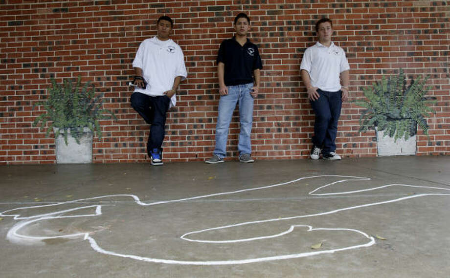 Jane Long Middle School students Adiel Gonzalez, 15, from left, and Eric Segovia, 15, and Fadi Sabah, 13, use a chalk outline as part of their public service video against gang activity, Photo: Julio Cortez, Chronicle