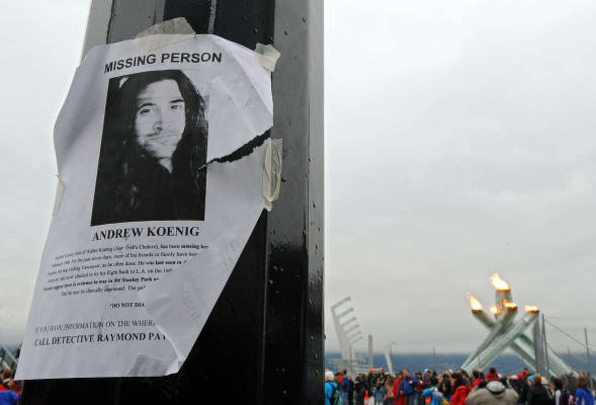 A missing-persons poster for actor Andrew Koenig is displayed on a light pole in front of the Olympic Cauldron in Vancouver.