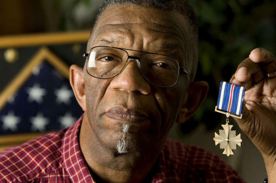 Retired Army Maj. Jimmy Johnson holds the Distinguished Flying Cross, one of his medals from Vietnam. Photo: Brett Coomer, Chronicle