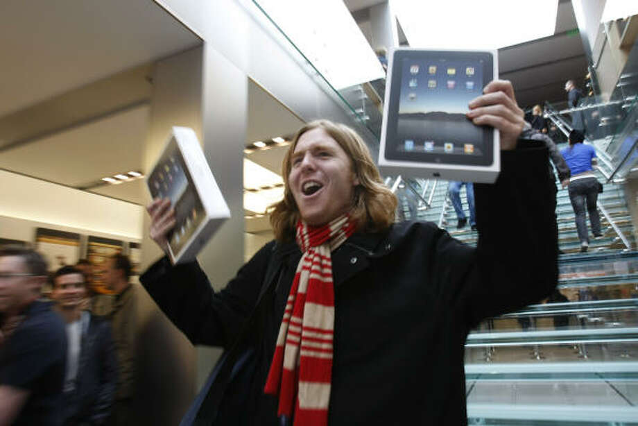 Apple said Monday that it sold more than 300,000 iPads on Saturday, the first day of sales. San Francisco's Andres Schobel holds up two of the first scooped up that day. Photo: Paul Sakuma:, AP