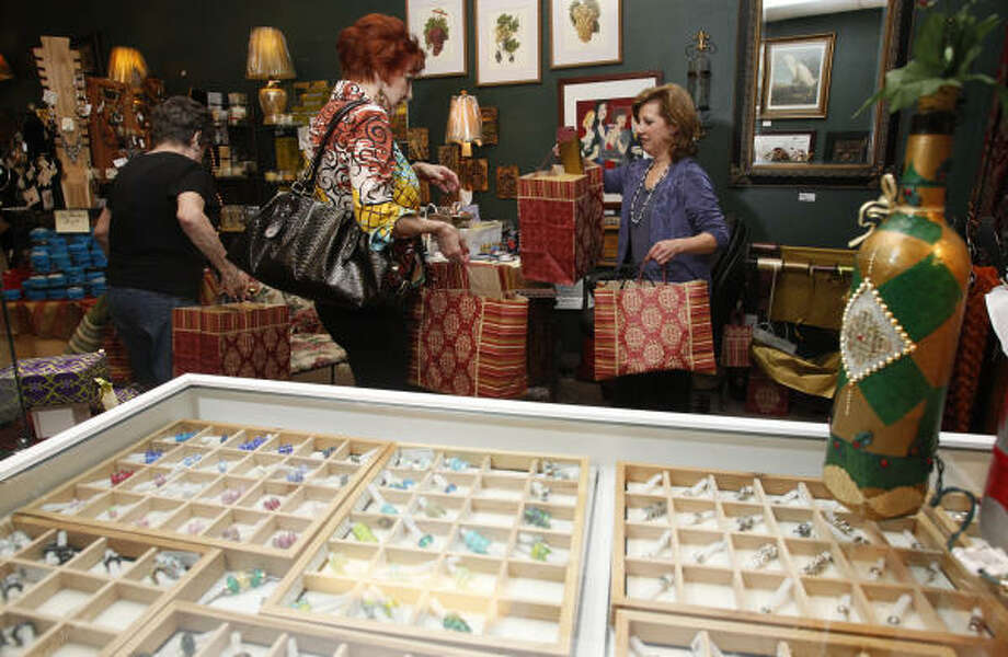A display of Trollbeads takes up the foreground as Sue Koym, of Seabrook, left, and Linda Costanza, of Clear Lake, finish making purchases with Southern Sophistication owner Jan Jouett, right, on Tuesday in Clear Lake City. Photo: Melissa Phillip:, Chronicle