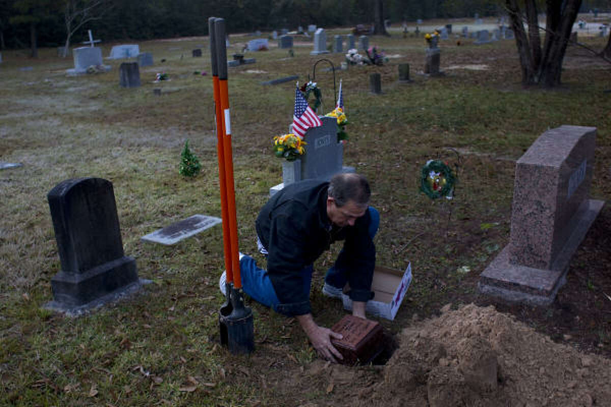 Travis Jones buries the ashes of his brother Claude during a service Tuesday at White Oak Cemetery in Porter.